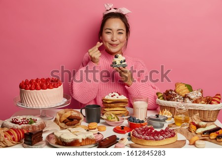Shot of adorable woman makes korean like sign, expresses affection, holds small delicious cupcake, celebrates birthday, isolated over rosy wall, made many tasty desserts. Cheat meal concept. #1612845283
