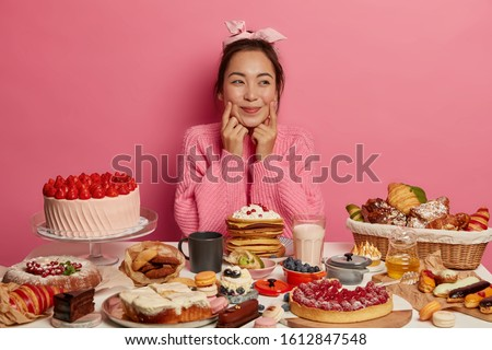 Photo of charming Korean woman keeps fingers on cheeks, surrounded with variery of sweet products, eats cakes, croissants and pancakes, tries to taste everything, wears headband and knitted jumper #1612847548