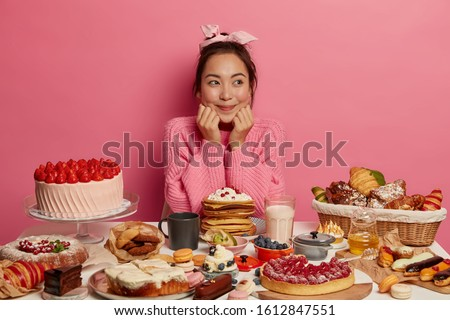 Photo of satisfied Asian woman sits at table overloaded with many desserts, breaks diet, has unhealthy nutrition, eats homemade cakes, croissants, dreams about eating sweets and not putting weight #1612847551