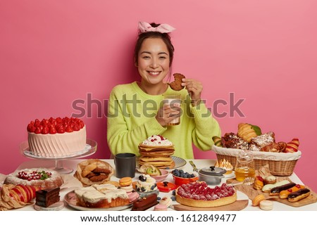 Happy woman in green jumper enjoys eating cookies and drinking milk, surrounded with many desserts, isolated on pink background, gets much calories during lunch. Addicted sweet lover eats yummy pastry #1612849477