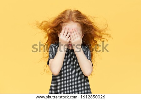 Isolated shot of timid little girl being shy, covering eyes. Red haired female child hiding tears behind her hands, crying. Caucasian kid playing seek and hide against blank yellow wall background #1612850026