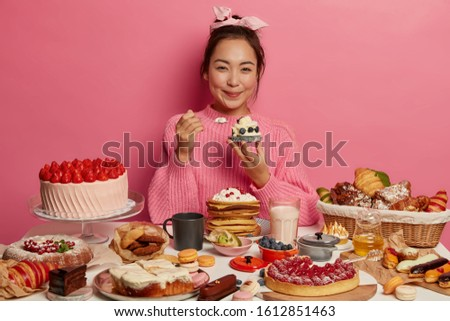 Woman eats with good appetite delicious creamy cupcake, enjoys sugary products, poses at festive table with various desserts, isolated over pink background. Junk food, dieting, culinary, bakery #1612851463