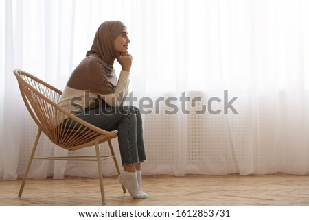 Morning Harmony. Muslim girl in hijab relaxing in wicker chair at home, resting head on hands and daydreaming against window, side view #1612853731