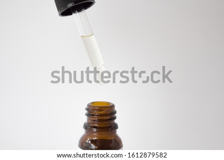 Dropper glass Bottle Mock-Up. Oily drop falls from cosmetic pipette on white background #1612879582