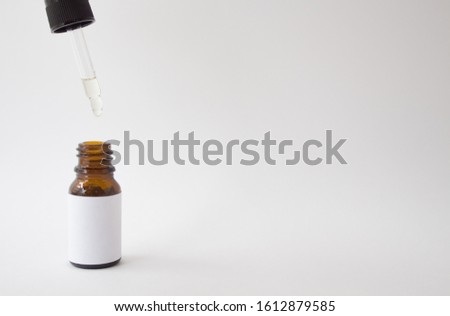Dropper glass Bottle Mock-Up. Oily drop falls from cosmetic pipette on white background #1612879585