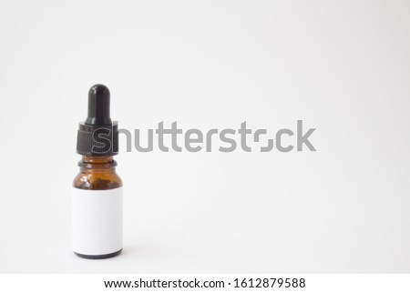 Dropper glass Bottle Mock-Up. Oily drop falls from cosmetic pipette on white background #1612879588