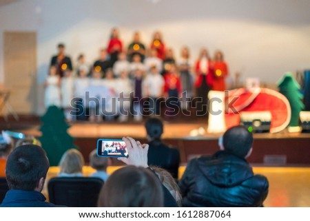Many parents are watching the kids performance in the hall. Children on stage perform in front of parents. Blurry #1612887064