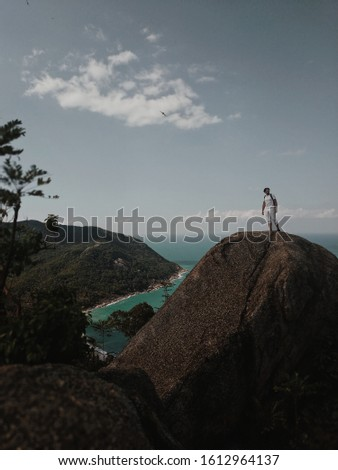 A man stands on the viewpoint over the bay.  Handsome guy in white clothes on a stone at a height above the ocean.  Nice view from the heights. #1612964137