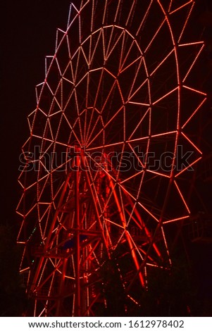 Ferris wheel at night glows with LED lights. Outlines of the wheel. Neon patterns in the dark #1612978402