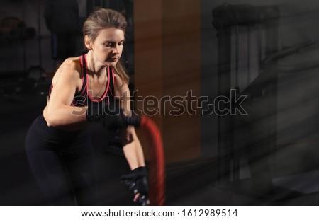caucasian female with battle ropes #1612989514