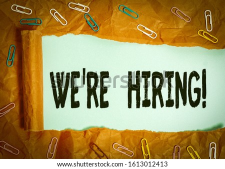 Handwriting text We Re Hiring. Concept meaning recently employ someone or pay him to do particular job Paper clip and torn cardboard placed above a plain pastel table backdrop. #1613012413