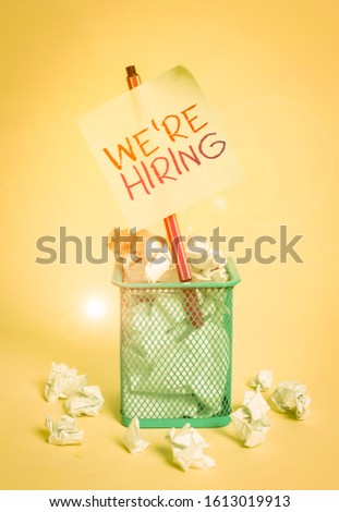 Writing note showing We Re Hiring. Business photo showcasing recently employ someone or pay him to do particular job crumpled paper and stationary with paper placed in the trash can. #1613019913