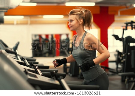 athletic caucasian female running on a treadmill #1613026621