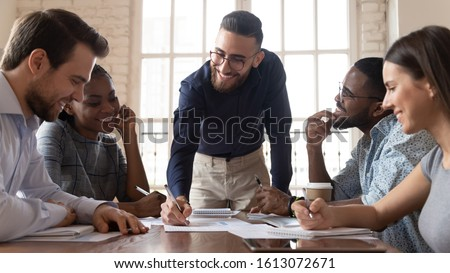 Smiling Arabian millennial businessman hold meeting with multiethnic colleagues explain financial paperwork at briefing, successful young Arabic male ceo or boss lead team briefing in office #1613072671
