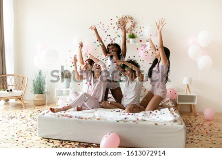 Smiling multiracial millennial girls in pajamas have fun in bedroom dance with colorful glitter confetti at hen party at home, happy diverse female friends laugh celebrate bachelorette bridal shower