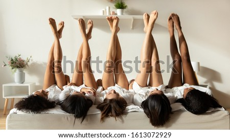 Diverse millennial girls lie upside down show legs celebrate bridal shower at home together, multiracial female friends in bathrobes have fun at spa pajama hen party in hotel, depilation concept #1613072929