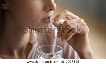Young female drink prescribed medicines with water suffer from headache or a depression, unhealthy woman take antibiotic or antidepressant meds, receive daily dose of vitamins, health problem concept #1613073145
