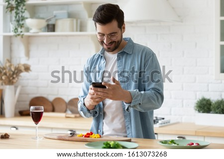 Head shot smiling young man using smartphone, chatting in social network while preparing food for vegetarian dinner at home. Happy millennial guy in eyeglasses web surfing recipe for meal in kitchen. #1613073268