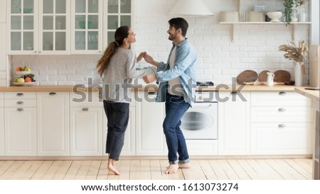 Full length happy family couple dancing barefoot on wooden heated floor in modern light kitchen. Overjoyed mixed race young married spouse enjoying leisure weekend time activity together at home. #1613073274