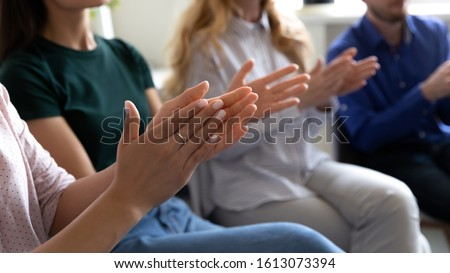 Office employees sit on chairs clap hands greeting presenter or speaker at group meeting close up, grateful audience applauding thanking coach for presentation or seminar for gained knowledge concept Royalty-Free Stock Photo #1613073394