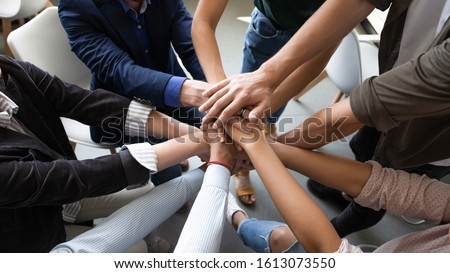 Top close up lot of hands stacked together as symbol concept of teambuilding, loyalty, amity and warm relations between office workers seminar participants, business success celebration, start of work #1613073550