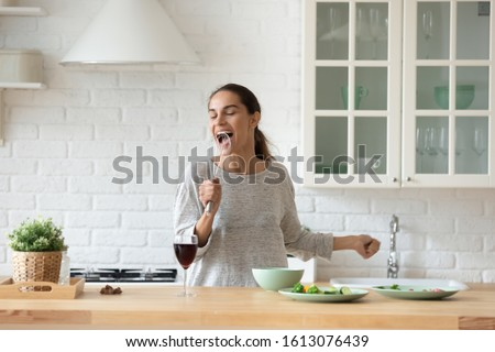 Head shot overjoyed young mixed race woman holding whisk, pretending to be singer, singer favorite pop song while cooking at modern kitchen. Happy lady having fun, cooking breakfast alone at home. #1613076439