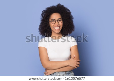 Confident happy african american young woman wearing spectacles, standing with folded hands head shot portrait. Smiling female client satisfied with optic clinic service isolated on blue background.
