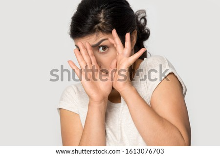 Isolated on grey studio background young indian afraid terrified woman hiding behind hands, trying to avoid something scared, making rejecting gesture, looking at camera, head shot close up portrait. Royalty-Free Stock Photo #1613076703