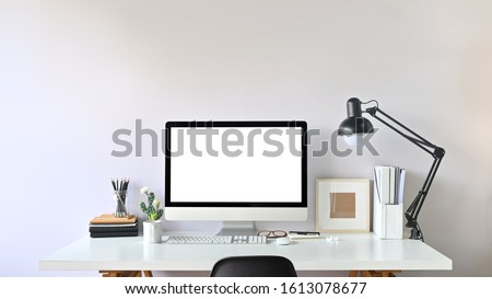 Photo of Contemporary Workspace. White blank screen monitor on modern working desk. Equipment on table. Modern office concept.  Royalty-Free Stock Photo #1613078677