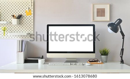 Front view shot of creative Work space. White blank screen computer on Office working desk. Equipment on table. Royalty-Free Stock Photo #1613078680