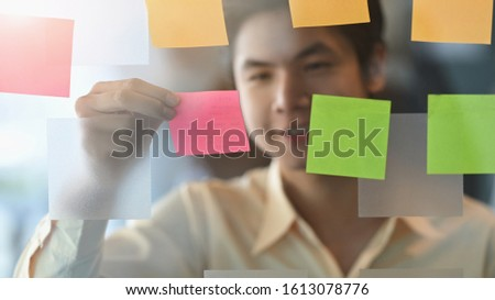 Photo of young businessman while sticky post it on glass. Meeting and sharing idea concept. Reminder schedule board. #1613078776