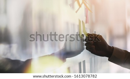 Closeup young businessman while sticky note on glass wall.Sticky note paper reminder schedule board. Brainstorming concept. #1613078782