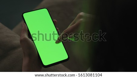 Young woman sitting on a couch and using smartphone with green screen