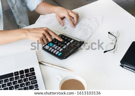 Pretty young Asian woman using calculator to calculate home expenses and tax in living room at home.  #1613103136