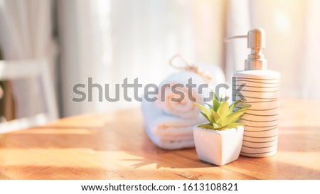 Spa concept includes white towels and liquid soap bottles, green plant on a white table in the hotel room for healthy skin and relaxation. #1613108821