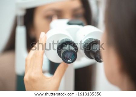 Diagnostic cabinet A young girl is diagnosed with vision and contact lenses are selected. #1613135350
