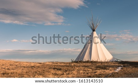Native American Teepee in the Grassy Plains at Sunset