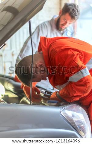 Male mechanics at the garage fixing a car. service and maintenance. car repair. fix a car. Hot bearded men #1613164096