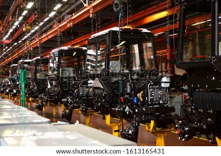 Tractor Manufacture works. Assembly line inside the agricultural machinery factory. Installation of parts on the tractor body. Tractor Manufacturing Facility. Tractors produced #1613165431