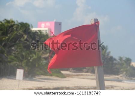 red flag waving on flagpole on beach #1613183749