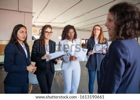 Mature colleague instructing younger colleagues. Professional business team listening mentor. Business concept #1613190661