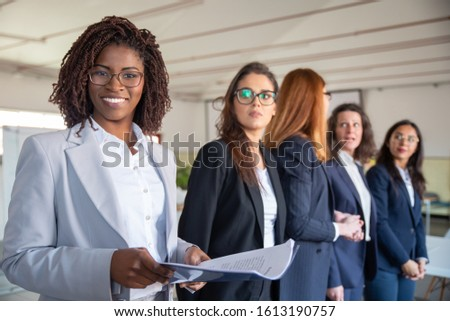 Smiling African American woman with paper documents. Professional business team standing in row. Business concept #1613190757