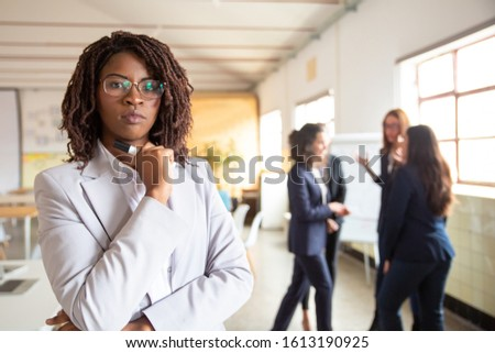 Confident African American businesswoman looking at camera. Front view of young woman with dreadlock holding marker. Female confidence concept #1613190925