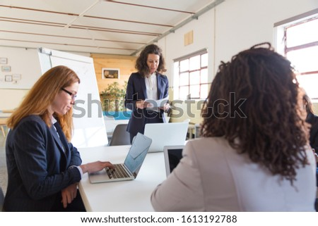 Professional businesswomen during presentation in office. Serious businesswoman standing with papers and female colleagues using laptops in office. Women in business concept #1613192788