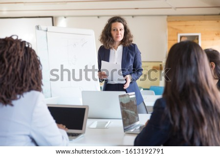 Serious businesswoman giving presentation to colleagues. Businesswomen using laptops and looking at female boss in office. Women in business concept #1613192791