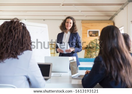 Smiling businesswoman giving presentation to colleagues. Businesswomen using laptops and looking at female boss in office. Women in business concept #1613193121