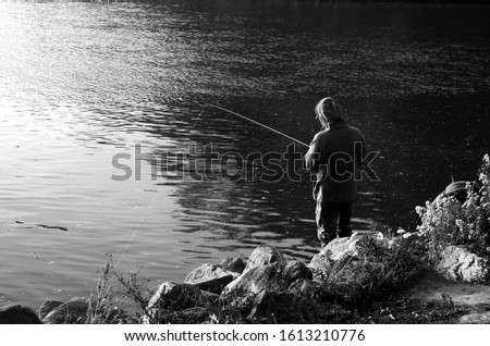 Black and white view of male fisherman angling in river. Angler fishing by river. Royalty-Free Stock Photo #1613210776