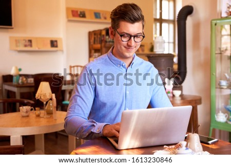 Smiling young businessman wearing shirt and eyeglasses while sitting at desk in a small cafe and working on notebook. Small business. #1613230846