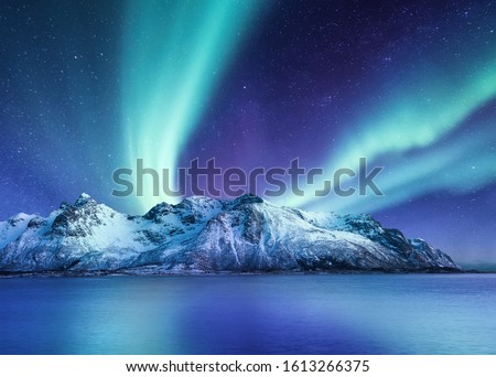 Aurora Borealis, Lofoten islands, Norway. Northen lights, mountains and reflection on the water. Winter landscape during polar lights. Norway travel - image #1613266375
