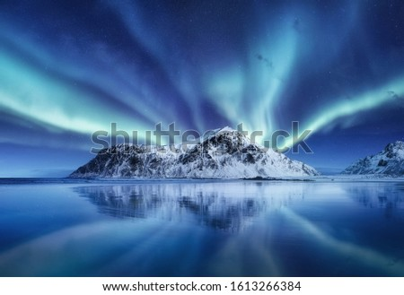 Aurora Borealis, Lofoten islands, Norway. Northen lights, mountains and reflection on the water. Winter landscape during polar lights. Norway travel - image #1613266384